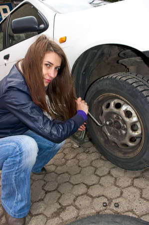 Young woman during the wheel changing Stock Photo - 9316314