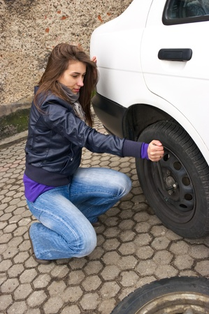 Young woman during the wheel changing Stock Photo - 9361408