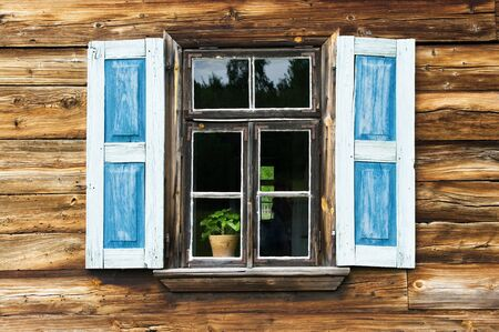 Window with blue shutters in old wooden wall photo