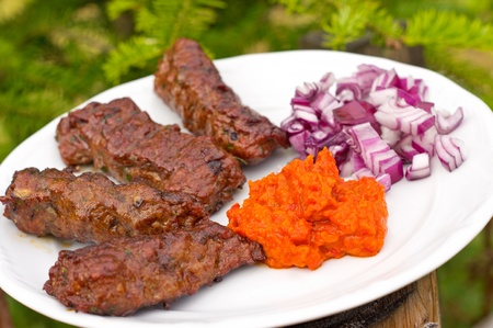 Traditional cevapcici with ajvar paste and red onion photo