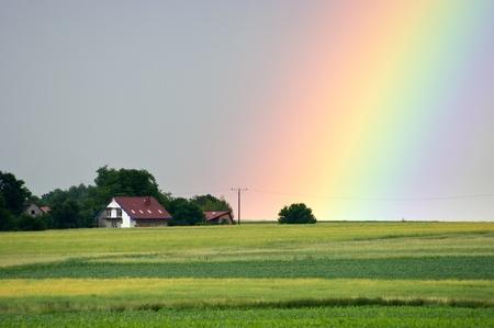 Beautiful rainbow over the village Stockfoto