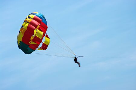 Silhouette of man with parachute on the sky