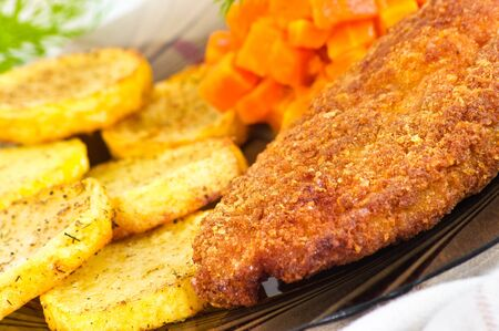 Parmesan breaded chicken breast with carrot and potato slices photo