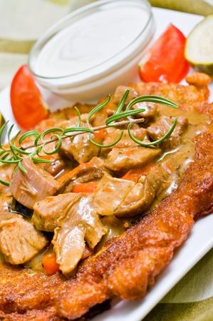 Traditional hungarian potato pancake with goulash
