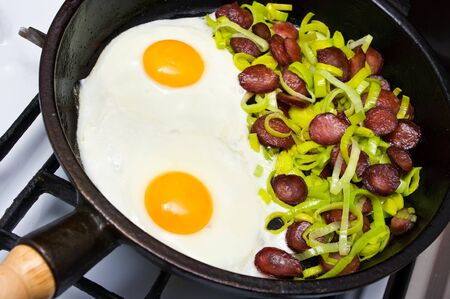 Fried egg with sausage and leek photo
