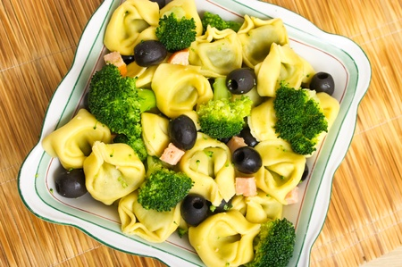 Tortellini salad with olives, salmon and broccoli photo