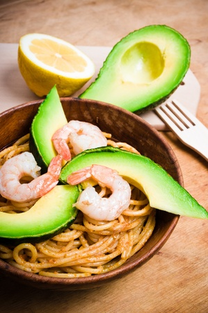 Spaghetti with shrimps, avocado and red pesto photo