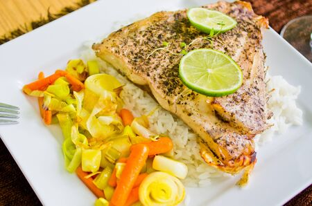 Portion of fish with rice and vegetables photo