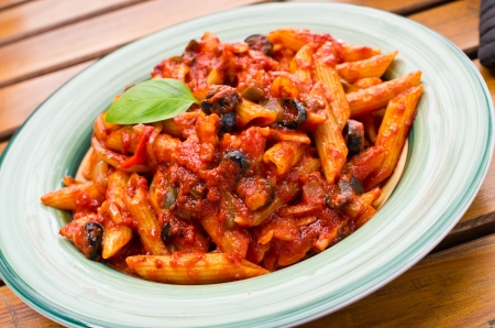 Penne arrabiata with basil leaf photo