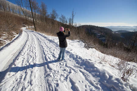 Woman taking photo by cell phone during the winter photo