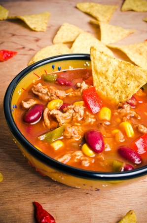Mexican soup (like chili con carne) with tacos photo
