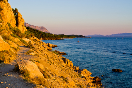 Narrow path on rocky Croatian seashore photo