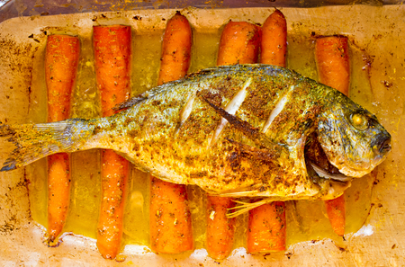 Dorade baked with curry on the carrots in oriental style photo