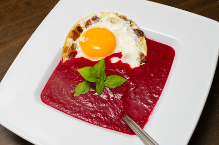 Beetroot cream soup with fried egg and crispy bacon photo