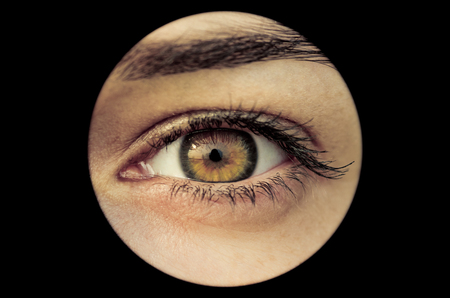 eye hole: Spying brown eye in the round black hole Stock Photo