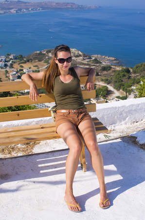 Young woman sitting on bench on top of the hill, Rhodes, Greece Stock Photo