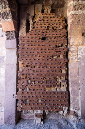 Old wooden gate covered by rusty metal