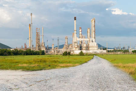 industria petroquimica: Petrochemical industry power with dirt road with green grass Editorial
