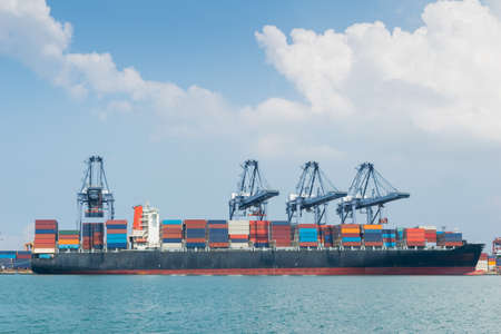 Container ship in asia port while load the job with blue sky