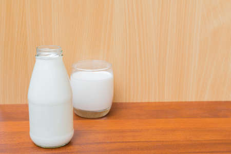 pasteurized: glass of milk and bottle of milk isolated on wood background