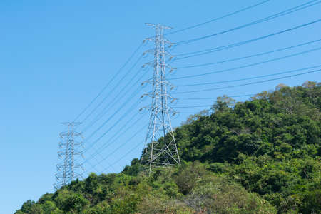 electric grid: transmission High voltage electricity pylon on mountain with blue sky background