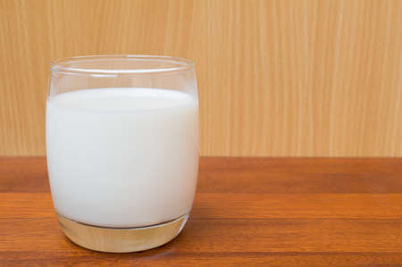 pasteurized: glass of milk isolated on wood background