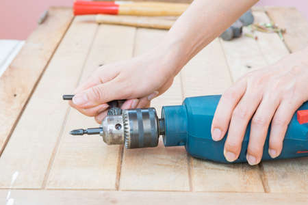 loose: People tighten or loose screw of the electric drill