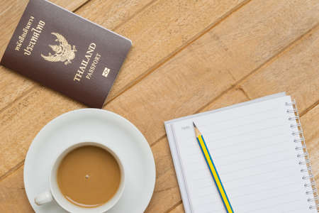 wood textures: Top view of hot coffee on white cup, passport and pencil on notebook on wood textures is diagonal for background Stock Photo