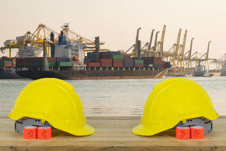 reflective: Container ship in asia port while load the job with yellow Safety Helmet for foreground