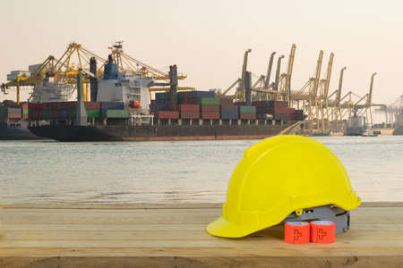 Container ship in asia port while load the job with yellow Safety Helmet for foreground
