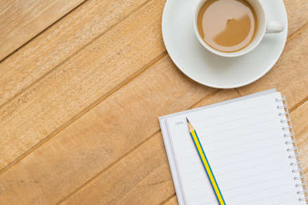wood textures: Top view of hot coffee on white cup and pencil on notebook on wood textures is diagonal for background