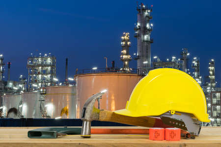 cutting tools: Front view of Yellow Safety Helmet, Hammer, Cutting tools on Oil refinery industry in night
