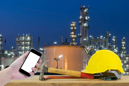 cutting tools: Front view of Hand holding the black smartphone and Yellow Safety Helmet, Hammer, Cutting tools on front of Oil refinery industry in night