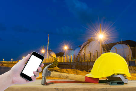 cutting tools: Front view of Hand holding the black smartphone and Yellow Safety Helmet, Hammer, Cutting tools on Oil refinery industry in evening Stock Photo