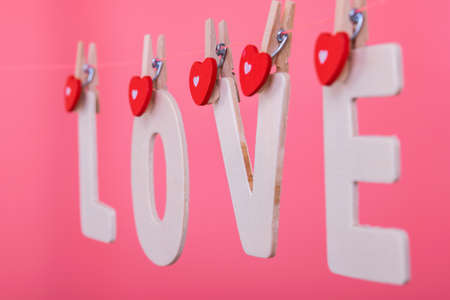 Word LOVE hang on pink color background, valentine