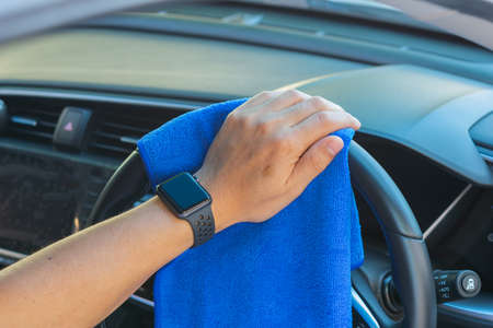 Closeup for man polishing cleaning car steering wheel with microfiber cloth