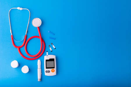 World diabetes day, Free Glucose Monitors on blue background with red Stethoscope put on blue on  top view Healthcare and medical concept Stock Photo