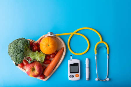 Diabetes monitor, diabetic measurement. World diabetes day concept. Yellow stethoscope check fruit on heart plate.