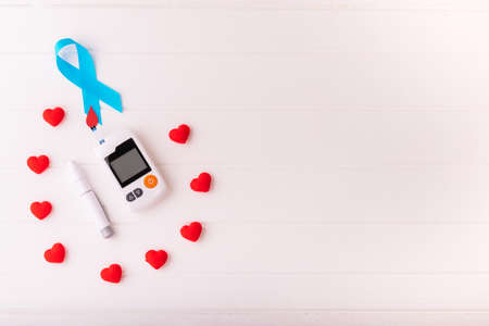 World diabetes day, Blue ribbon awareness with red blood drop on a white wood background, Glucose Monitors equipment with red heart on white background. Healthcare and medical concept