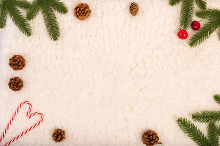 Christmas fir branches on edge frame, pine cones, red berries and candy cane on soft white background. Christmas and New Year background. Stock Photo