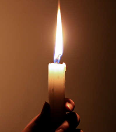 Holding a candle in darkness. photo