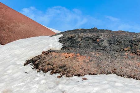 snow on lava stone on mount etna
