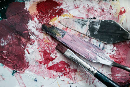 old paintbrush and knife with colors