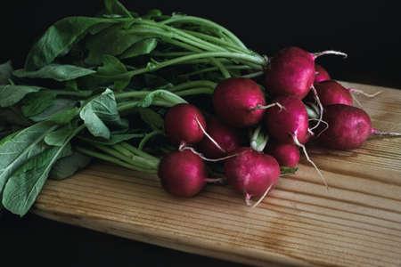 red radish on wooden board in dark