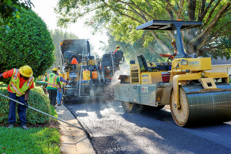 WINDERMERE, FLORIDA, USA - MAY 18, 2017: Asphalt paving crew using heavy machinery resurfacing a residential neighborhood on a bright Florida morning. 版權商用圖片 - 83579278