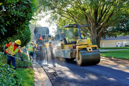 WINDERMERE, FLORIDA, USA - MAY 18, 2017: Asphalt paving crew using heavy machinery repaving a residential neighborhood on a bright Florida morning. 新聞圖片