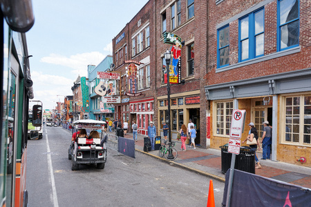 NASHVILLE, TN, USA - APRIL 14, 2017: Nashvilles historic Broadway street, home to Ernest Tubb Record Shop, noisy and full of bars, entertainment, country music and visited by countless tourists on foot, in golf carts or busses.