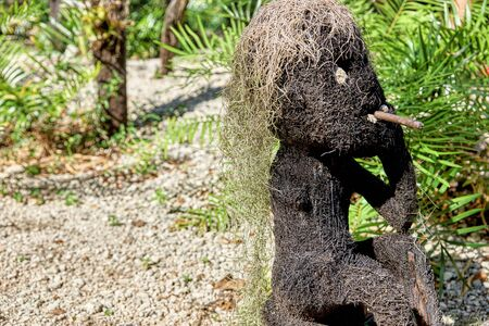 Funny statue of a man smoking made from coconut or other tree fiber, with hair of Spanish moss. Object found in a forest, with tropical plants in the background.