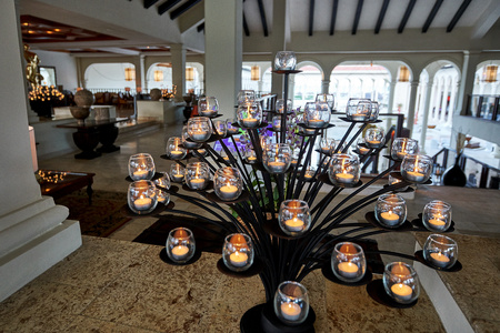 PUNTA CANA, DOMINICAN REPUBLIC - MARCH 19, 2017: A creative tree formed from natural candles inside the lobby of the Paradisus Hotel in Playa Bavaro in the Caribbean. The light is natural twilight. 新聞圖片