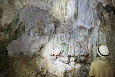 Person admiring a wall inside a cave in natural light as provided by a hole in the ceiling. Cave formations and small stalactites in nuanced colors ranging from green to light purple.